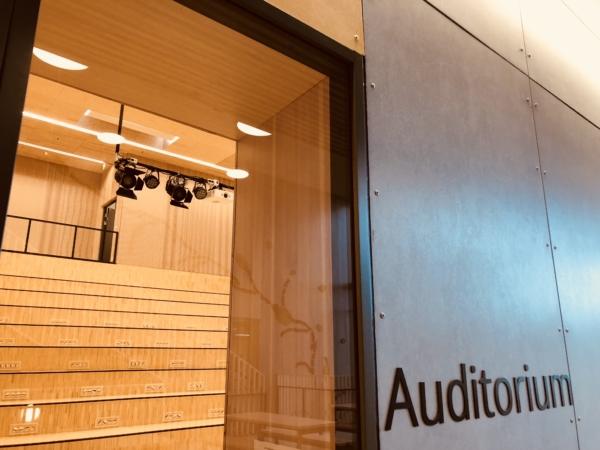Ser inn i gjennom vinduet på auditoriet mot amfi og lys og projektor rigg